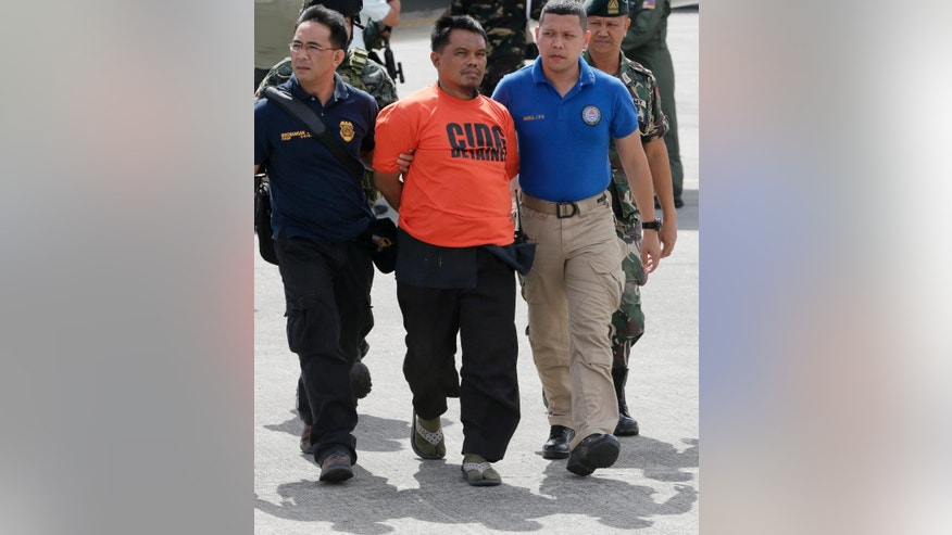 Army and police forces escort handcuffed Mohammad Ali Tambako, the leader of a Muslim rebel group in the south who has been linked to bombings and a beheading and accused of protecting two terror suspects wanted by the United States, shortly upon arrival at Villamor Air Base at suburban Pasay city south of Manila, Philippines Monday, March 16, 2015. Tambako and five of his men were arrested late Sunday while the militants were traveling in a motorcycle sidecar taxi to a seaport in southern General Santos city. (AP Photo/Bullit Marquez)