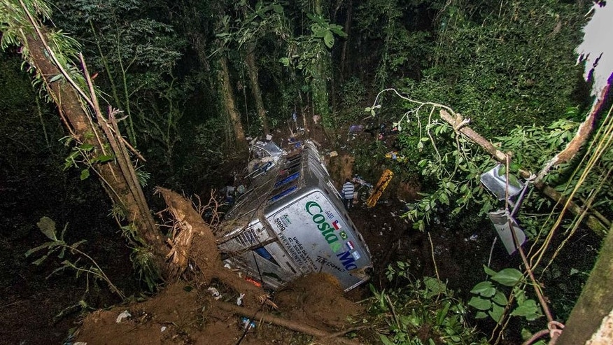 Rescue personnel work at the site where a tourist bus crashed killing at least 54 people, near the city of Joinville, southern state of Santa Catarina, Brazil, Sunday, March 15, 2015. The Brazilian government raised the death toll of a bus accident to 54 while police continued their search for more victims Sunday in the rugged lands of southern Brazil. The dead include at least eight young children, three adolescents, 24 women and 14 men, the government of Santa Catarina state said in a statement earlier Sunday, when the death toll stood at 49. (AP Photo/Eduardo Valente-Agencia O Globo) BRAZIL OUT
