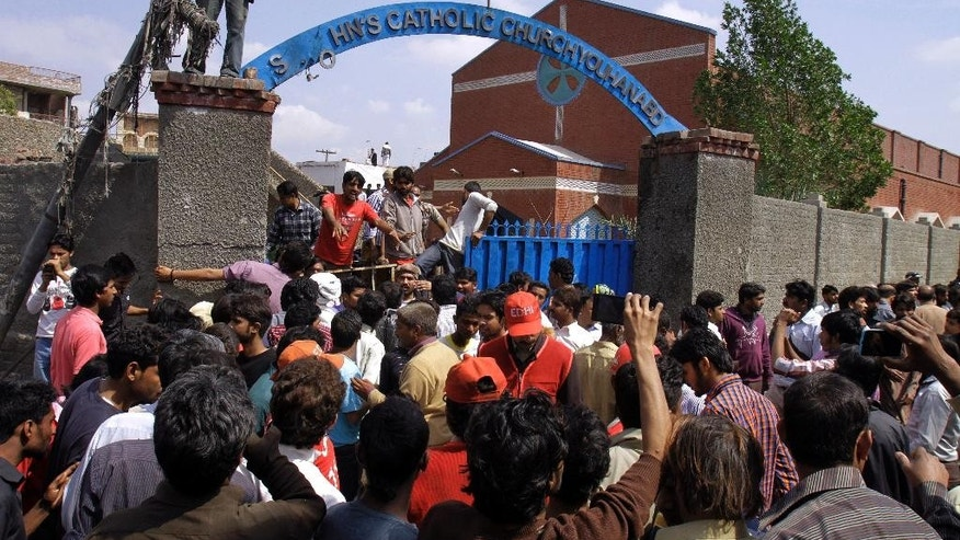 Pakistani Christians and rescue workers gather outside a church damaged from a suicide bombing attack in Lahore, Pakistan, Sunday, March 15, 2015. Suicide bombers exploded themselves near two churches in the eastern city of Lahore on Sunday as worshippers were gathered inside, killing at least a dozen people, officials said, in the latest attack against religious minorities in the country. (AP Photo/K.M. Chaudary)