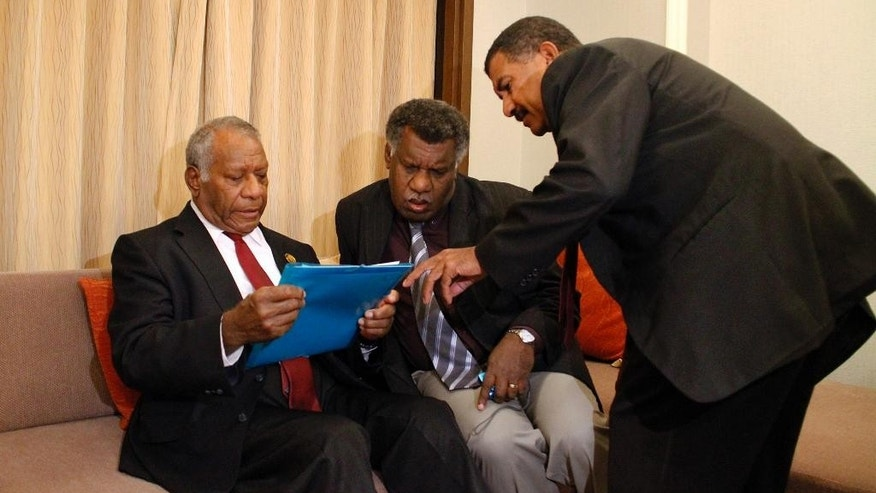 "Vanuatu President Baldwin Lonsdale, left, Minister for Climate Change James Bule, center, and National Disaster Management Office Director Shadrack Rubart Welegtabit discuss before an interview in their hotel room in Sendai, Miyagi prefecture, northeastern Japan, Monday, March 16, 2015 while attending a U.N. conference on disaster risk reduction. The Pacific island nation of Vanuatu has lost years of development progress and must ""start over"" following a powerful cyclone that destroyed or damaged 90 percent of the buildings on the main island of Port Vila, the country's president said Monday. (AP Photo/Koji Ueda)"