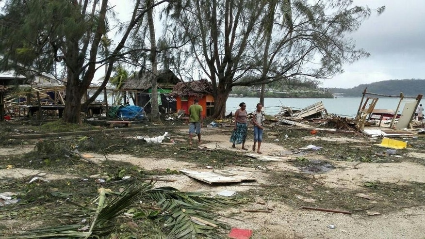 In this photo provided by China's Xinhua News Agency, locals walk past debris in Port Vila, Vanuatu, after Cyclone Pam ripped through the tiny South Pacific archipelago,  Sunday, March 15, 2015. Packing winds of 270 kilometers (168 miles) per hour, Cyclone Pam tore through Vanuatu early Saturday, leaving a trail of destruction. (AP Photo/Xinhua, Luo Xiangfeng) NO SALES