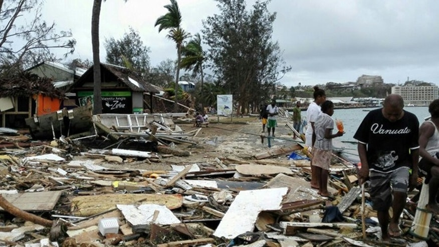 March 15, 2015: In this photo provided by China's Xinhua News Agency, locals walk past debris in Port Vila, Vanuatu, after Cyclone Pam ripped through the tiny South Pacific archipelago.
