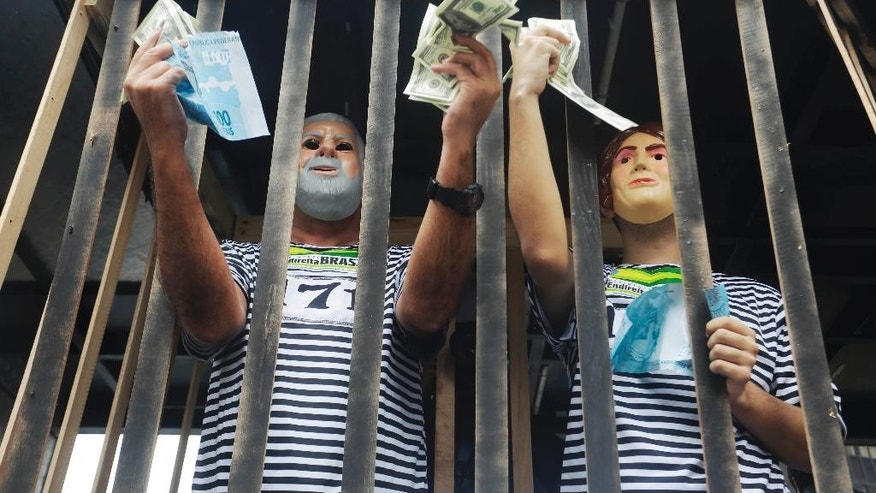 Demonstrators wearing masks depicting the former President Luiz Inacio Lula da Silva, left, and Brazil's President Dilma Rousseff holds fake money inside a mock jail during a protest march demanding the impeachment of Brazil's President Dilma, over an alleged scheme of corruption that siphoned money from the state-owned oil company Petrobras, in Sao Paulo, Brazil, Sunday, March 15, 2015. (AP Photo/Nelson Antoine)