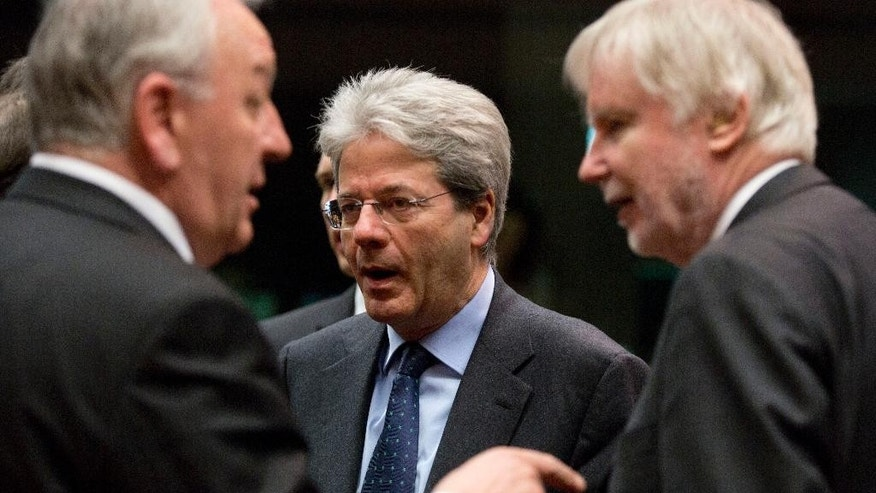 Italian Foreign Minister Paolo Gentiloni, center, waits for the start of a meeting of EU foreign ministers at the EU Council building in Brussels on Monday, March 16, 2015. The European Union is debating ways to back peace talks in Libya but is unlikely to launch any security mission until stability returns to the conflict-torn country. (AP Photo/Virginia Mayo)