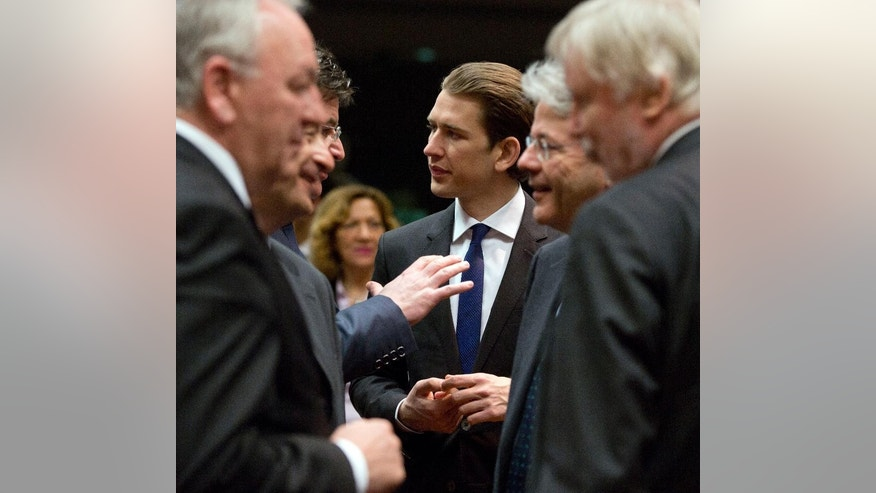 Austrian Foreign Minister Sebastian Kurz, center, speaks with counterparts during a meeting of EU foreign ministers at the EU Council building in Brussels on Monday, March 16, 2015. The European Union is debating ways to back peace talks in Libya but is unlikely to launch any security mission until stability returns to the conflict-torn country. (AP Photo/Virginia Mayo)