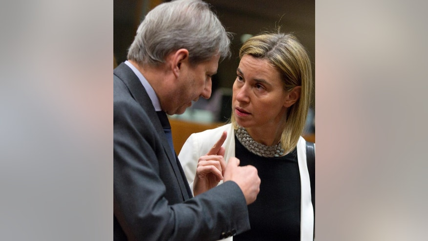 European Union High Representative Federica Mogherini, right, speaks with EU Commissioner for Enlargement Johannes Hahn during a meeting of EU foreign ministers at the EU Council building in Brussels on Monday, March 16, 2015. The European Union is debating ways to back peace talks in Libya but is unlikely to launch any security mission until stability returns to the conflict-torn country. (AP Photo/Virginia Mayo)