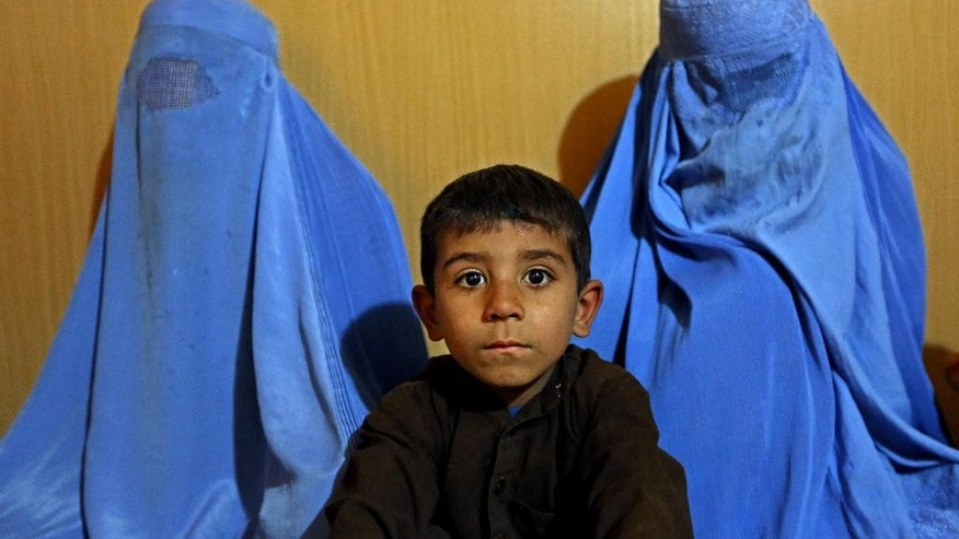 In Wednesday, March 11, 2015 photo, an Afghan refugee family who arrived to Afghanistan through Pakistan's border crossing, pose for a photograph at the International Organization for Migration center in Torkham, east of Kabul, Afghanistan. Since January, almost 50,000 Afghan families have passed through Torkham, double the amount of all refugees returning through the border town in 2014, according to the International Organization for Migration. Many say they fled Pakistan over increased harassment by police who told them to return to Afghanistan, a country many have never even seen, putting new pressure on both countries to find solutions to the decades-old flow of refugees. (AP Photo/Rahmat Gul)