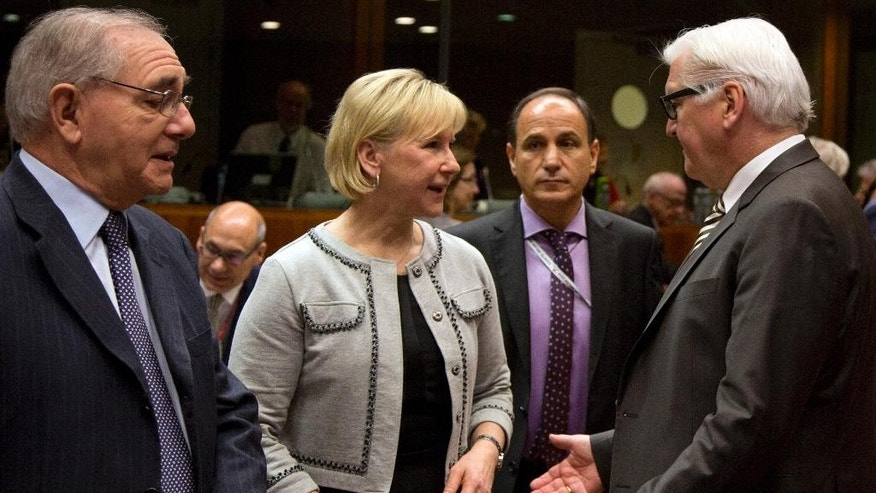 CAPTION CORRECTS ID AND JOB TITLE FROM EUROPEAN UNION HIGH REPRESENTATIVE FEDERICA MOGHERINI TO SWEDEN'S FOREIGN MINISTER MARGOT WALLSTROM  Sweden's Foreign Minister Margot Wallstrom, center, speaks with German Foreign Minister Frank-Walter Steinmeier, right, during a meeting of EU foreign ministers at the EU Council building in Brussels on Monday, March 16, 2015. The European Union is debating ways to back peace talks in Libya but is unlikely to launch any security mission until stability returns to the conflict-torn country. (AP Photo/Virginia Mayo)