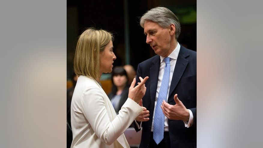 European Union High Representative Federica Mogherini, left, speaks with British Foreign Minister Philip Hammond during a meeting of EU foreign ministers at the EU Council building in Brussels on Monday, March 16, 2015. The European Union is debating ways to back peace talks in Libya but is unlikely to launch any security mission until stability returns to the conflict-torn country. (AP Photo/Virginia Mayo)