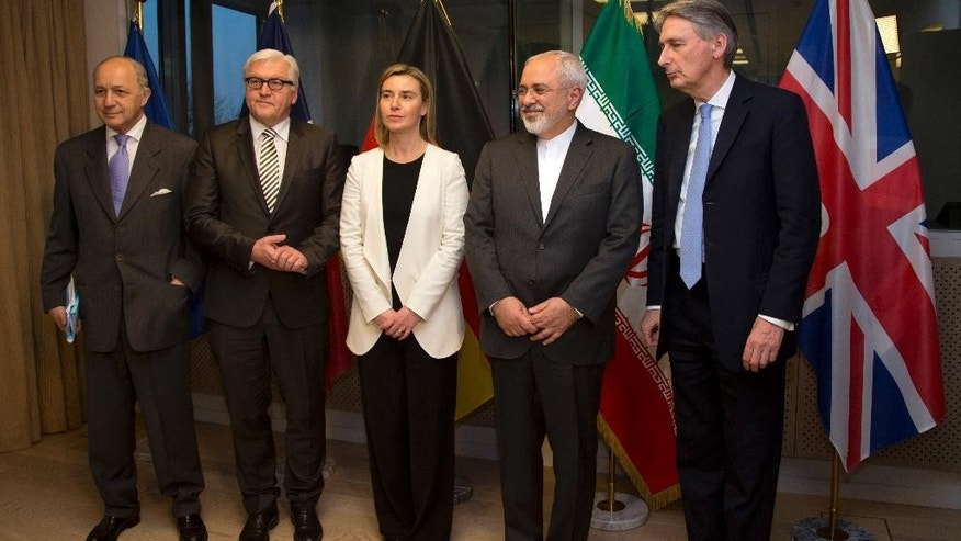 From left, French Foreign Minister Laurent Fabius, German Foreign Minister Frank-Walter Steinmeier, European Union High Representative Federica Mogherini, Iran's Foreign Minister Mohammad Javad Zarif and British Foreign Minister Philip Hammond stand for a group photo prior to a meeting in Brussels on Monday, March 16, 2015. European Union foreign ministers hold talks with Iran's top diplomat on Monday to try to advance an agreement on the Islamic Republic's nuclear program two weeks ahead of a deadline for an accord to be reached. (AP Photo/Virginia Mayo)