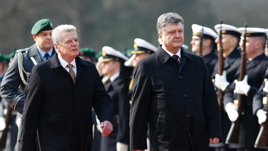 German President Joachim Gauck, left, and Ukraine's President Petro Poroshenko, right, review the honor guards during the welcoming ceremony prior to a meeting at Bellevue Palace in Berlin, Monday, March 16, 2015. (AP Photo/Markus Schreiber)