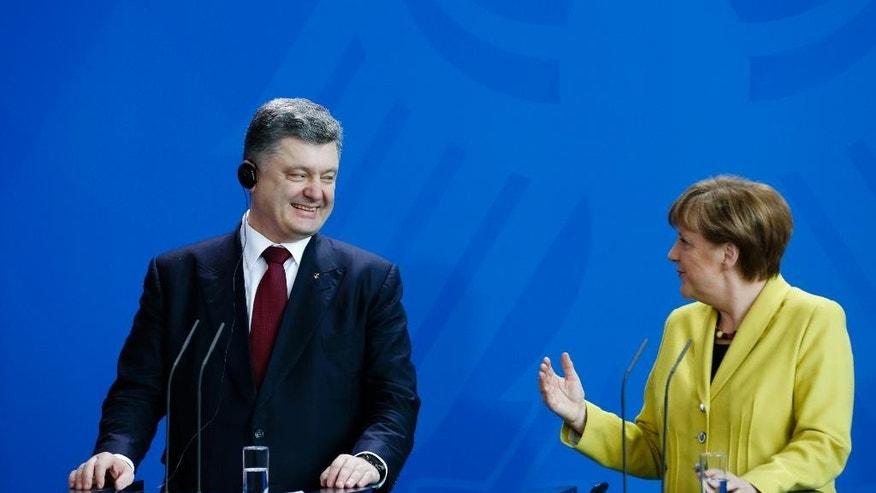 German Chancellor Angela Merkel, right, and Ukraine's President Petro Poroshenko, left, brief the media during a news conference after a meeting at the chancellery in Berlin, Germany, Monday, March 16, 2015. (AP Photo/Markus Schreiber)