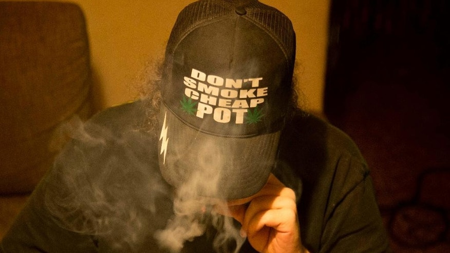 In this Oct. 21, 2013 photo, Daniel, who did not want to give his last name, smokes marijuana he grew in a hydroponics garden inside his apartment in Mexico City. The market for gourmet weed is still minuscule next to the multibillion-dollar marijuana export trade dominated by the cartels. Like others, Daniel ordered seeds online from a company in Spain, opting for a U.K-originated strain known as Exodus Cheese. (AP Photo/Eduardo Verdugo)