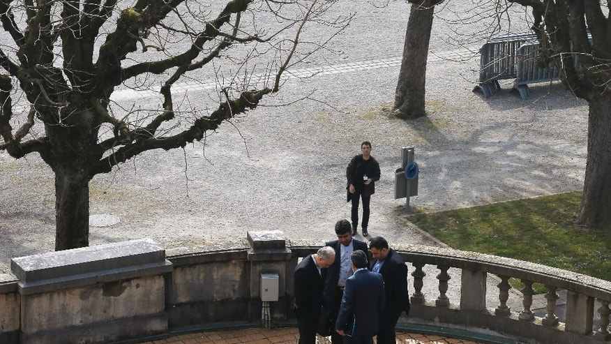 Iran's nuclear chief Ali Akbar Salehi, left, and other Iranian negotiators talk in private conference outside the Beau-Rivage hotel, following a meeting between U.S. Secretary of State John Kerry and Iran's Foreign Minister Javad Zarif over Iran's nuclear program, in Lausanne, Switzerland, Monday March 16, 2015.  The US have repeated calls for Syrian President Bashar Assad to step down, but Assad said Monday that only Syrians can decide his future. (AP Photo/Brian Snyder, pool)