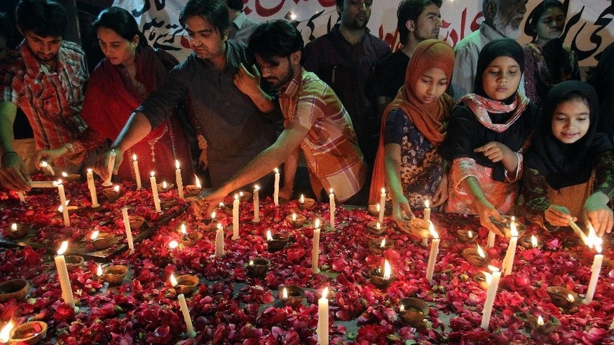 Pakistani children and members of a civil society light candles during a vigil for the victims of a suicide bombing attack on churches, Sunday, March 15, 2015 in Karachi, Pakistan. Suicide bombers exploded themselves near two churches in the eastern city of Lahore on Sunday as worshippers were gathered inside, killing at least a dozen people, officials said, in the latest attack against religious minorities in the country. (AP Photo/Fareed Khan)