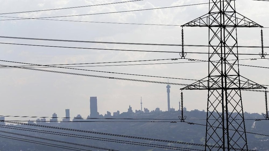 In this photo taken Tuesday, March 10, 2015 electricity pylons cross the skyline of Johannesburg city, background. Rolling blackouts have become a common drudgery in the country with the government warning that forced outages will will continue for years. (AP Photo/Themba Hadebe)