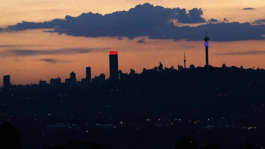 In this photo taken Tuesday, March 10, 2015 the sun sets behind the skyline of Johannesburg city, background. Rolling blackouts have become a common drudgery in the country with the govrnment warning that forced outages will will continue for years. (AP Photo/Themba Hadebe)
