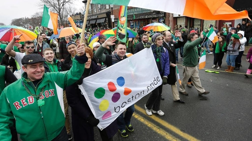Freddy Murphy, of Boston, front left, waves an Irish flag while marching with the LGBT community advocacy group Boston Pride during the St. Patrick's Day parade, Sunday, March 15, 2015, in Boston's South Boston neighborhood. Until now, gay rights groups have been barred by the South Boston Allied War Veterans Council from marching in the parade, which draws as many as a million spectators each year. (AP Photo/Steven Senne)