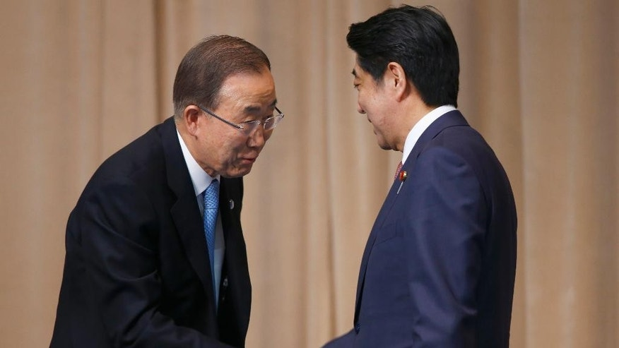 U.N. Secretary General Ban Ki-moon, left, shakes hands with Japanese Prime Minister Shinzo Abe after a symposium of the 70th anniversary of the United Nations at the UN University in Tokyo, Monday, March 16, 2015. (AP Photo/Shizuo Kambayashi)