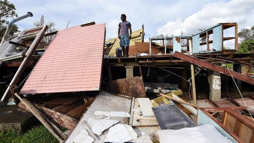 "Adrian Banga surveys his destroyed house in Port Vila, Vanuatu in the aftermath of Cyclone Pam, Monday, March 16, 2015. Vanuatu's President Baldwin Lonsdale said Monday that the cyclone that hammered the tiny South Pacific archipelago over the weekend was a ""monster"" that has destroyed or damaged 90 percent of the buildings in the capital and has forced the nation to start anew. (AP Photo/Dave Hunt, Pool)"