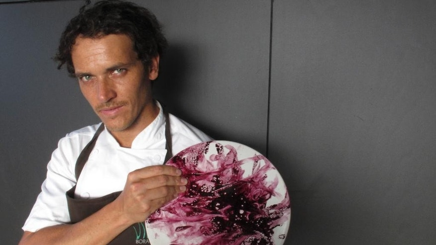 "In this Feb. 14, 2015 photo, chef Rodolfo Guzman, owner of the Borago restaurant, holds up a plate smeared with maqui berries, in Santiago, Chile. The restaurant has been named in the Latin American section of the San Pellegrino's World's Best Restaurant list. ""We've developed in our kitchens all these foods that the Mapuche had been eating for hundreds of years."" (AP Photo/Luis Andres Henao)"