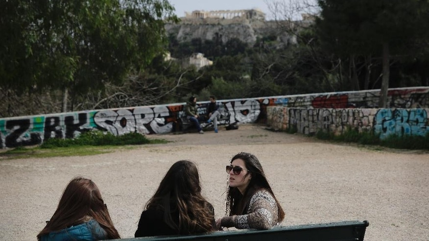 Young women sit on a bench with the ancient Acropolis hill visible in the background, in Athens, Tuesday, March 17, 2015. The leader of Greece has called for joint talks with his counterparts from Germany, France and the European Union executive in the hope of getting past an impasse in the country's bailout negotiations. (AP Photo/Petros Giannakouris)