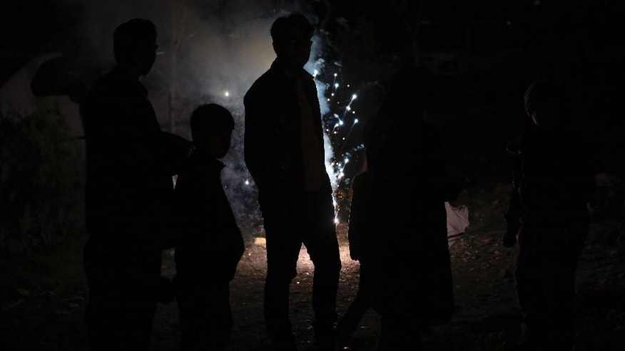 Iranians watch a firework display during Chaharshanbe Souri, or Wednesday Feast, an ancient Festival of Fire, on the eve of the last Wednesday of the solar Persian year, in Tehran, Iran, Tuesday, March 17, 2015.  In Tehran, people lit bonfires in public places, set off fireworks and sent wish lanterns floating into the night sky as part of the annual ritual that dates back to at least 1700 B.C. and is linked to Zoroastrianism. Since the 1979 Islamic Revolution, hard-liners have discouraged the celebration, viewing it as a pagan holdover from pre-Islamic times. (AP Photo/Vahid Salemi)