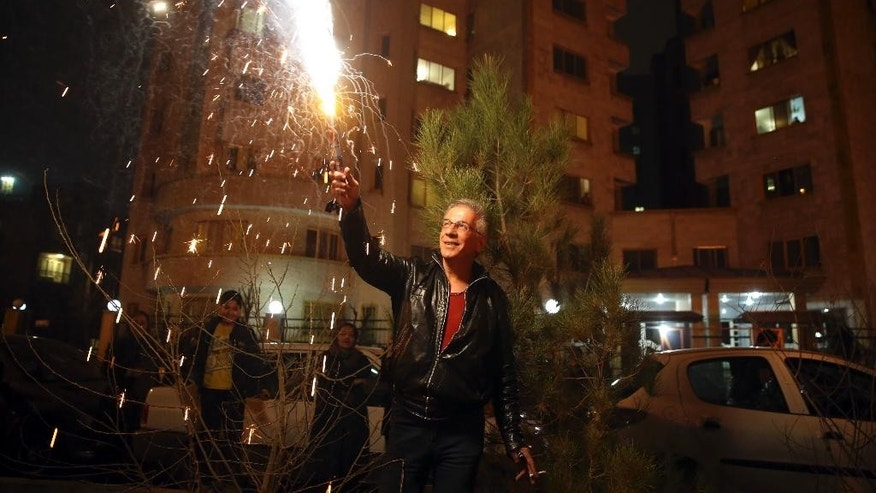 An man holds up a firework during Chaharshanbe Souri, or Wednesday Feast, an ancient Festival of Fire, on the eve of the last Wednesday of the solar Persian year, in Tehran, Iran, Tuesday, March 17, 2015. In Tehran, people light bonfires, set off fireworks and send wish lanterns into the night sky as part of an annual ritual that dates back to at least 1700 B.C. and is linked to Zoroastrianism. Since the 1979 Islamic Revolution, hard-liners have discouraged the celebration, viewing it as a pagan holdover from pre-Islamic times. (AP Photo/Vahid Salemi)