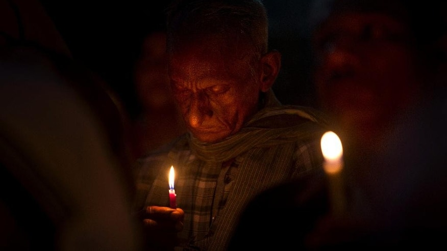 An Indian man prays as Christians and others hold a candle light vigil to condemn the gang rape of a nun at a Christian missionary school in eastern India outside the Sacred Heart cathedral in New Delhi, India, Monday, March 16, 2015.  According to police a nun in her 70s was gang-raped by a group of bandits when she tried to prevent them from committing a robbery in the Convent of Jesus and Mary School in West Bengal state's Nadia district. The attack early Saturday is the latest crime to focus attention on the scourge of sexual violence in India. (AP Photo/Saurabh Das)