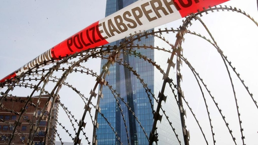 Barbed wire is fixed in front of the new headquarters of the European Central Bank in Frankfurt, Germany, Tuesday, March 17, 2015. The new premises of the ECB will be inaugurated on Wednesday, clashes between police and demonstrators are expected. Words read: Police Cordon.  (AP Photo/Michael Probst)