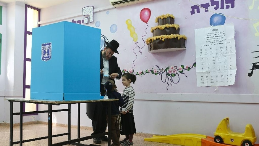 An Ultra orthodox Jew lprepares to  vote in Bnei Brak, Israel, Tuesday, March 17, 2015.  Israelis are voting in early parliament elections following a campaign focused on economic issues such as the high cost of living, rather than fears of a nuclear Iran or the Israeli-Arab conflict. .(AP Photo/Oded Balilty)