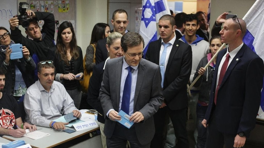 Zionist Union leader Isaac Herzog accompanied by his wife Michal prepares to cast his vote  in Tel Aviv, Israel, Tuesday, March 17, 2015. Israelis are voting in early parliament elections following a campaign focused on economic issues such as the high cost of living, rather than fears of a nuclear Iran or the Israeli-Arab conflict. (AP Photo/Ariel Schalit)