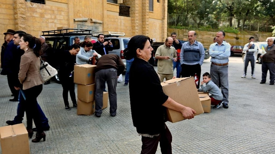 Iraqi Chaldean Christians, who fled their home from Iraq, receive humanitarian aid at the Chaldean Archbishopric, in Baabda, east of Beirut, Lebanon, Tuesday, March 17, 2015. Syrian and Iraqi Christians are pleading for more international assistance from new homes in Lebanon where they recently arrived after fleeing attack by militants from the Islamic State group. (AP Photo/Bilal Hussein)