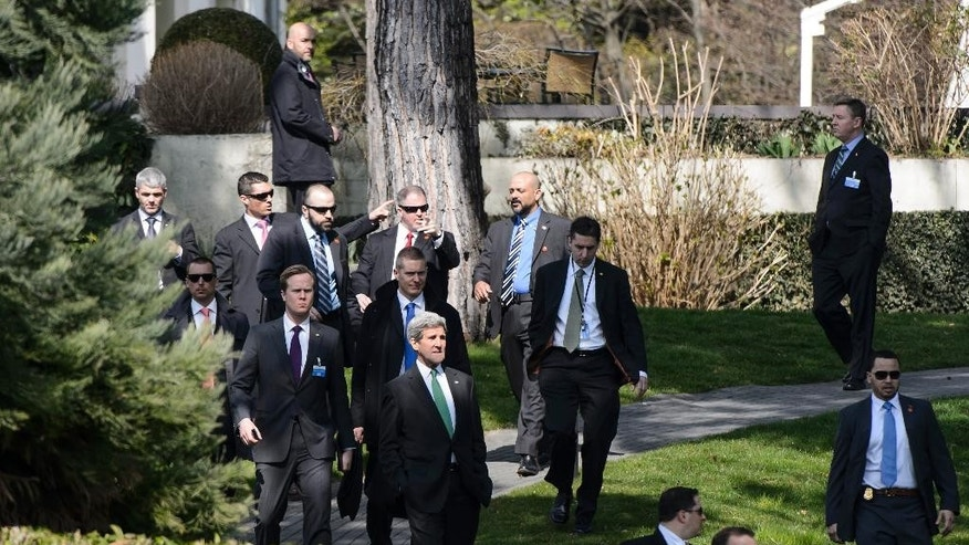 John Kerry, U.S. Secretary of State, center, walks outside the hotel during a break after a bilateral meeting with Iranian Foreign Minister Mohammad Javad Zarif, for a new round of Nuclear  Talks, in Lausanne, Switzerland, Tuesday, March 17, 2015.  (AP Photo/Keystone, Jean-Christophe Bott)