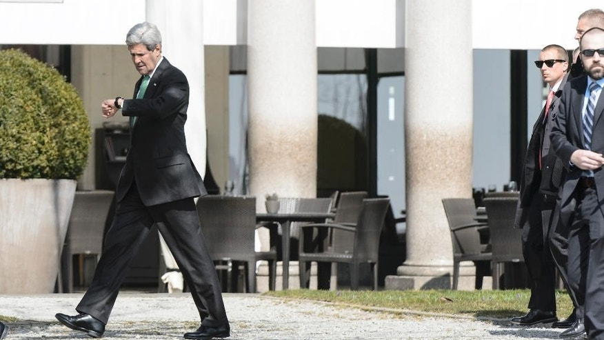 John Kerry, U.S. Secretary of State, left,walks outside the hotel during a break after a bilateral meeting with Iranian Foreign Minister Mohammad Javad Zarif, for a new round of Nuclear  Talks, in Lausanne, Switzerland, Tuesday, March 17, 2015.  (AP Photo/Keystone, Jean-Christophe Bott)