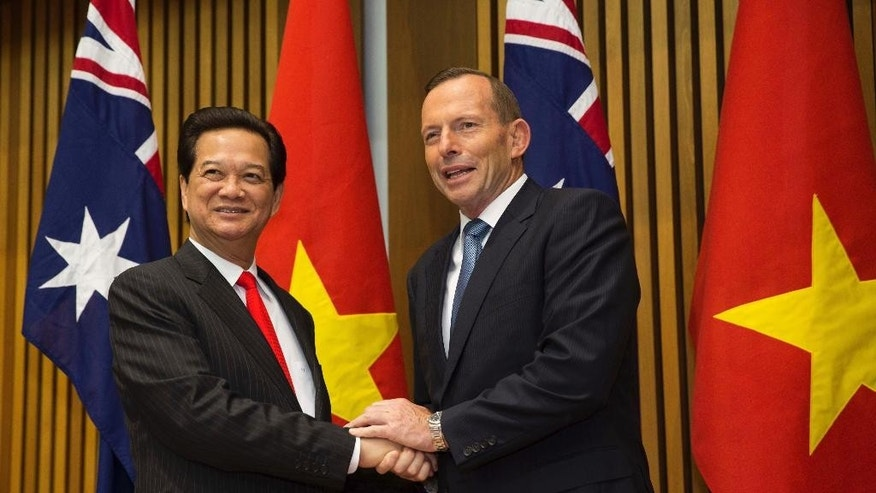 "Vietnamese Prime Minister Nguyen Tan Dung and Australian Prime Minister Tony Abbott shake hands before witnessing the signing of a ""friendship agreement"" between their countries at Parliament House in Canberra, Australia Wednesday, March 18, 2015.  They met to discuss the strengthening of co-operation between their two countries.  (AP Photo/Andrew Taylor)"