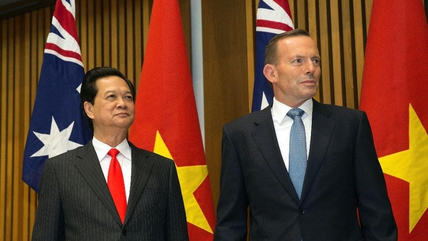 Vietnamese Prime Minister Nguyen Tan Dung and Australian Prime Minister Tony Abbott wait to witness the signing of a friendship agreement between their countries at Parliament House in Canberra, Australia Wednesday, March 18, 2015. Vietnam and Australia agreed to closer security ties during a meeting of the two nation's prime ministers as Australia continues to balance its relationship with its biggest trading partner China and relations with other neighbors in the Asia-Pacific region. (AP Photo/Andrew Taylor)