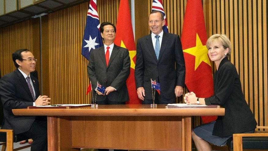 Vietnamese Prime Minister Nguyen Tan Dung, center left, and Australian Prime Minister Tony Abbott, center right, witness the signing of a friendship agreement by Vietnamese Minister and Chairman of the Government Office Nguyen Van Nen, left, and Australian Foreign Minister Julie Bishop at Parliament House in Canberra, Australia Wednesday, March 18, 2015. Vietnam and Australia have agreed to closer security ties during a meeting of the two nation's prime ministers as Australia continues to balance its relationship with its biggest trading partner China and relations with other neighbors in the Asia-Pacific region. (AP Photo/Andrew Taylor)