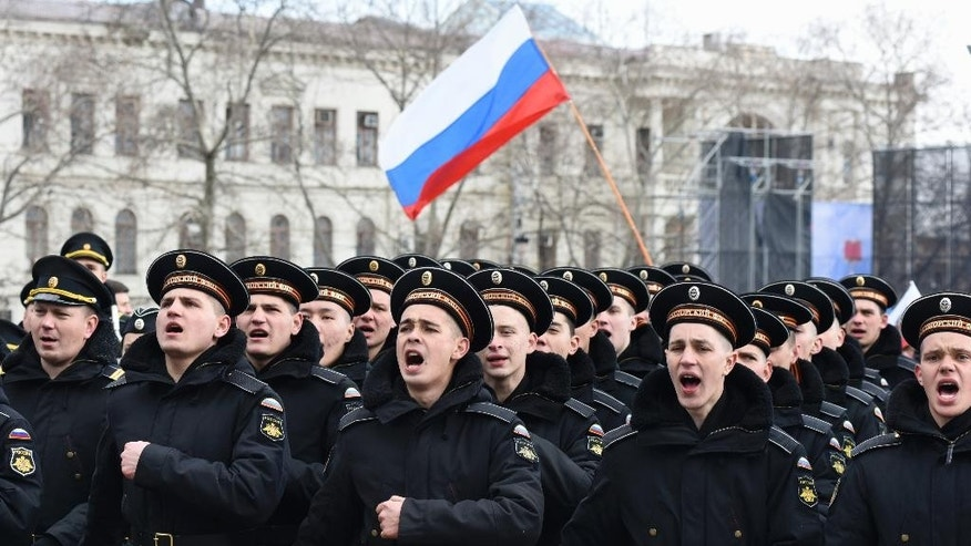 Russian Black Sea fleet sailors shout as they march during a military parade in Sevastopol, Crimea, Wednesday, March 18, 2015. Russia on Wednesday marked the one year anniversary of the annexation of Ukraine's Crimea peninsula. (AP Photo/Alexander Polegenko)
