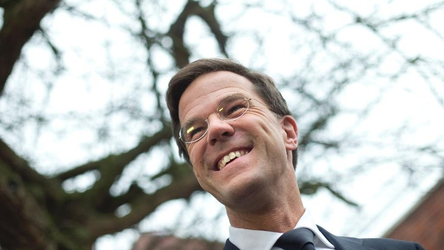 Dutch Prime Minister Mark Rutte answers questions from reporters after casting his ballot in The Hague, Netherlands, Wednesday, March 18, 2015. The Dutch are going to the polls to elect 12 provincial councils, in a vote that could have profound consequences for the ruling coalition of Rutte. (AP Photo/Peter Dejong)