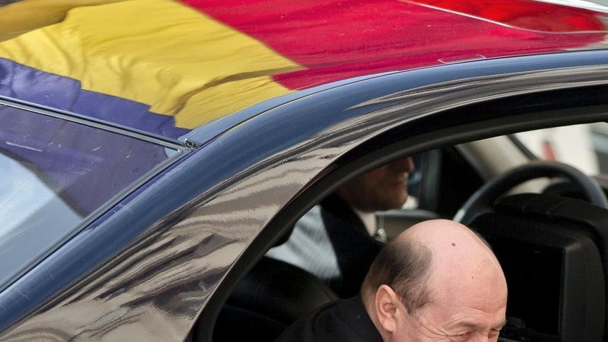 Former Romanian President Traian Basescu arrives at the prosecutor's office in Bucharest, Romania, Wednesday, March 18, 2015. Prosecutors have informed Basescu he is under a criminal investigation for making threatening remarks to Senator Gabriela Vranceanu Firea, a political rival. The investigation did not start while Basescu was still in office because he had immunity from prosecution as president. (Vadim Ghirda)