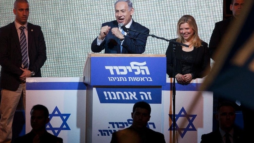 Israeli Prime Minister Benjamin Netanyahu greets supporters at the party's election headquarters In Tel Aviv. Wednesday, March 18, 2015. Exit polls from Israel's national elections showed Prime Minister Benjamin Netanyahu's Likud party nearly deadlocked with Isaac Herzog's center-left Zionist Union. (AP Photo/Dan Balilty)