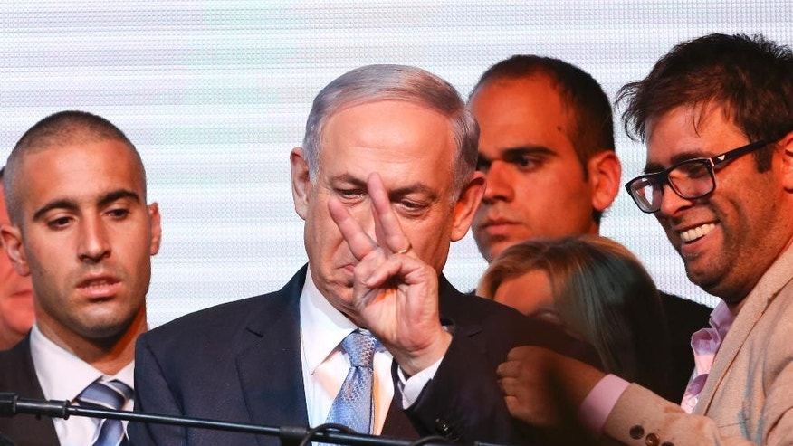 Israeli Prime Minister Benjamin Netanyahu greets supporters at the party's election headquarters In Tel Aviv. Wednesday, March 18, 2015. Exit polls from Israel's national elections showed Prime Minister Benjamin Netanyahu's Likud party nearly deadlocked with Isaac Herzog's center-left Zionist Union. (AP Photo/Oded Balilty)