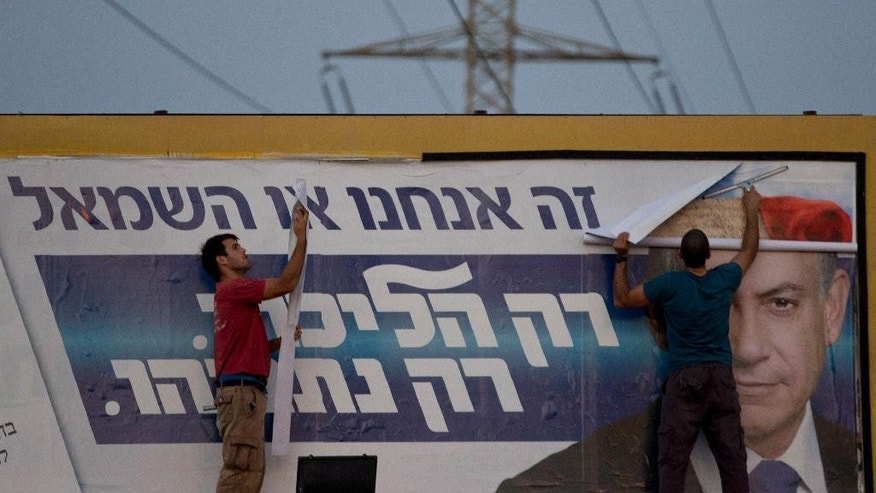 """Workers remove an election campaign billboard of the Likud party showing Israeli Prime Minister Benjamin Netanyahu in Ramat Gan, Israel, Wednesday, March 18, 2015, a day after Israel held legislative election. Netanyahu's right-wing Likud Party scored a resounding victory in Israel's election, final results showed Wednesday, a stunning turnaround after a tight race that had put his lengthy rule in jeopardy. The Hebrew says, """"It's us or the left, only Likud, only Netanyahu."""" (AP Photo/Ariel Schalit)"""