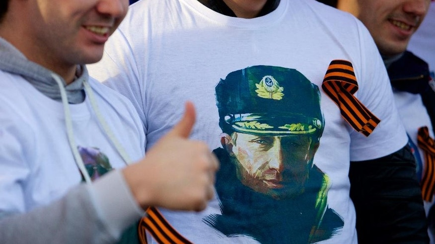 March 18, 2015: Demonstrators wearing t-shirts depicting Russian President Vladimir Putin gather for a concert to mark the one year anniversary of the annexation of Ukraine's Crimea peninsula, outside the Kremlin in  Moscow, Russia.