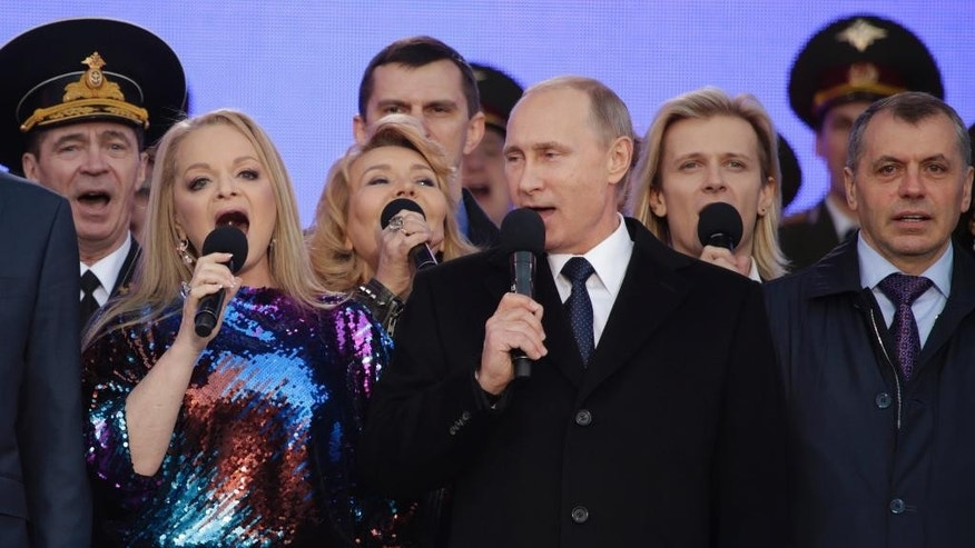 "Russian President Vladimir Putin, center, sings the national anthem at a rally marking the one year anniversary of the annexation of Ukraine's Crimea peninsula, in downtown Moscow, Russia, Wednesday, March 18, 2015. Speaking to tens of thousands of supporters just outside the Kremlin walls, Putin has described Russia's annexation of Ukraine's Crimean Peninsula as a move to protect ethnic Russians and regain the nation's ""historic roots."" At left is Russian singer Larisa Dolina. (AP Photo/Pavel Golovkin)"