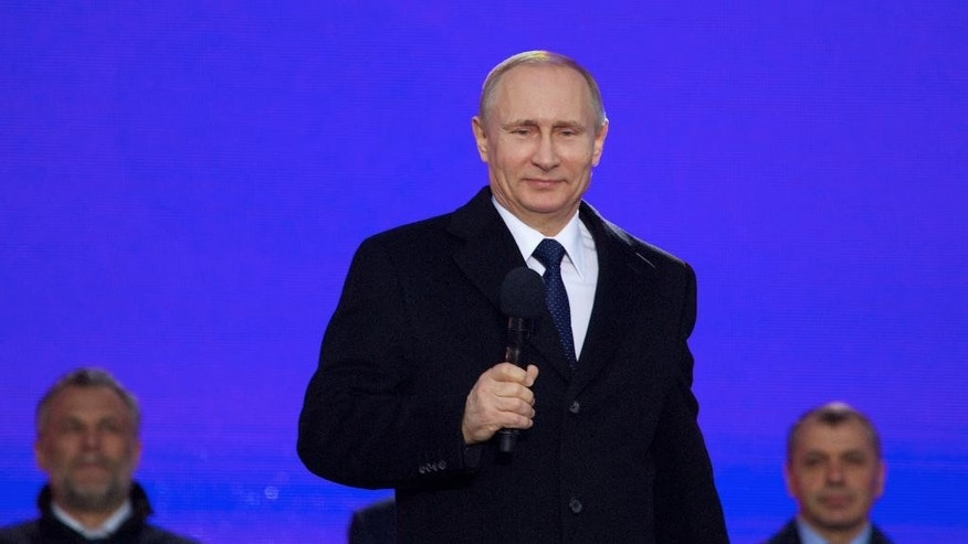 "Russian President Vladimir Putin pauses as he speaks at a rally marking the one year anniversary of the annexation of Ukraine's Crimea peninsula, outside the Kremlin in Moscow, Russia, Wednesday, March 18, 2015. Speaking to tens of thousands of supporters just outside the Kremlin walls, Putin has described Russia's annexation of Ukraine's Crimean Peninsula as a move to protect ethnic Russians and regain the nation's ""historic roots.""  (AP Photo/Pavel Golovkin)"