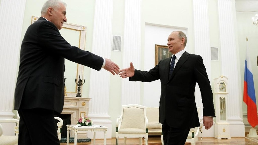 Russian President Vladimir Putin, right, greets the leader of Georgia's breakaway province of South Ossetia Leonid Tibilov during their meeting in the Kremlin in Moscow, Russia, Wednesday, March 18, 2015. (AP Photo/Maxim Shipenkov, Pool)