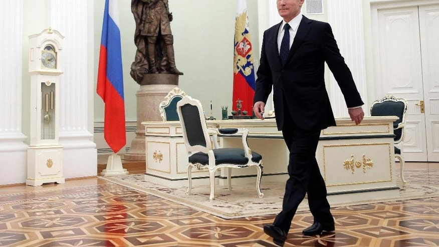 Russian President Vladimir Putin heads for a meeting with the leader of Georgia's breakaway province of South Ossetia Leonid Tibilov at the Kremlin, Moscow, Russia, Wednesday, March 18, 2015. (AP Photo/Maxim Shipenkov, Pool)