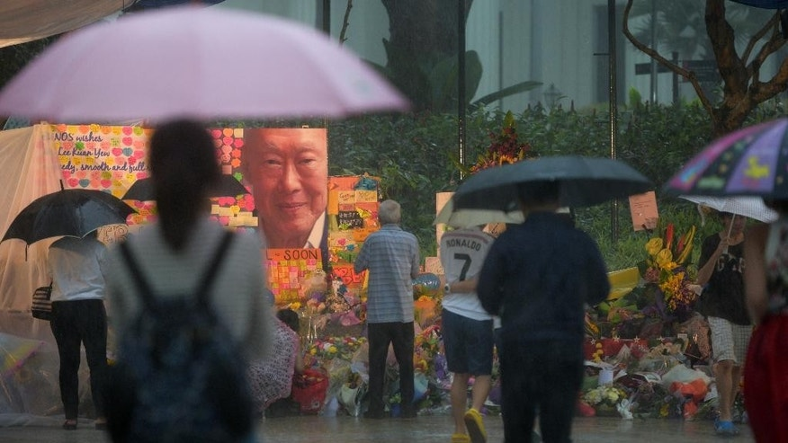 Well wishers brave heavy rain to place flowers and messages of support for Singapore's founding prime minister Lee Kuan Yew at Singapore General Hospital where he has been warded for the last 6 weeks on Sunday, March 22, 2015 in Singapore. As the health of Lee deteriorated on the weekend, thousands of Singaporeans visited his hospital and a community center to leave flowers, gifts and emotional messages of support. (AP Photo/Joseph Nair)